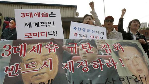 North Korean defectors with a banner showing photos of North Korean leader Kim Jong Il, right, his late father Kim Il Sung, left, and his youngest son Kim Jong Un, during a rally against the North&#39;s succession in Seoul, South Korea, Friday, Oct. 8, 2010. The letters on a banner read &#34;We denounce family&#39;s succession through three generations.&#34; &#40;AP Photo&#47;Ahn Young-joon&#41; <span class=meta>(AP Photo&#47; Ahn Young-joon)</span>