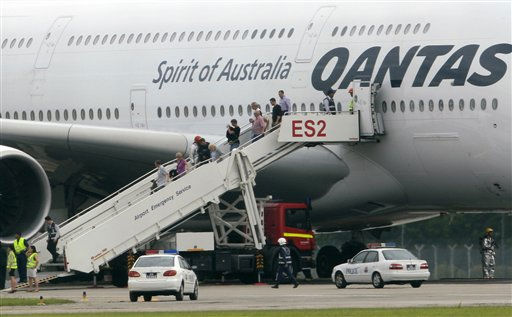 Passengers are evacuated from a Qantas plane which made an emergency landing in Singapore&#39;s Changi International Airport Thursday, Nov. 4, 2010 in Singapore. The Qantas jetliner made an emergency landing Thursday in Singapore with 459 people aboard, after one of its four engines shut down over western Indonesia and following witness reports of a blast that sent debris hurtling to the ground. The airliner denied there had been any explosion, and said the plane landed safely with no injuries. &#40;AP Photo&#47;Wong Maye-E&#41; <span class=meta>(AP Photo&#47; Wong Maye-E)</span>