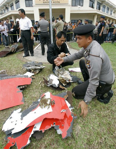Indonesian police officers inspect parts of a Qantas jetliner that were found in the area, at the local police headquarters in Batam, Indonesia, Thursday, Nov. 4, 2010. The jetliner made an emergency landing Thursday in Singapore with 459 people aboard, after one of its four engines shut down over western Indonesia and following witness reports of a blast that sent debris hurtling to the ground. &#40;AP Photo&#47;Tundra Laksamana&#41; <span class=meta>(AP Photo&#47; Tundra Laksamana)</span>