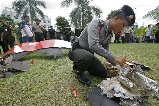 An Indonesian police officer inspects parts of a Qantas jetliner that were found in the area, at the local police headquarters in Batam, Indonesia, Thursday, Nov. 4, 2010. The jetliner made an emergency landing Thursday in Singapore with 459 people aboard, after one of its four engines shut down over western Indonesia and following witness reports of a blast that sent debris hurtling to the ground. &#40;AP Photo&#47;Tundra Laksamana&#41; <span class=meta>(AP Photo&#47; Tundra Laksamana)</span>