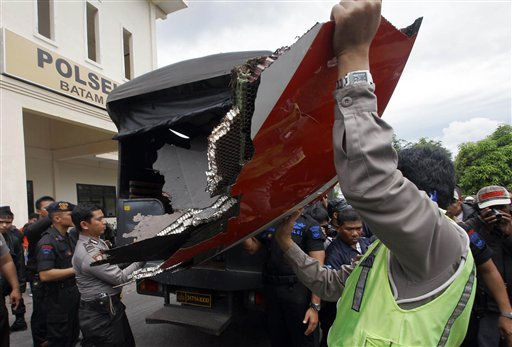 Indonesian police officers carry a part of a Qantas jetliner that was found in the area, at the local police headquarters in Batam, Indonesia, Thursday, Nov. 4, 2010. A Qantas jetliner made an emergency landing Thursday in Singapore with 459 people aboard, after one of its four engines shut down over western Indonesia and following witness reports of a blast that sent debris hurtling to the ground. &#40;AP Photo&#47;Tundra Laksamana&#41; <span class=meta>(AP Photo&#47; Tundra Laksamana)</span>