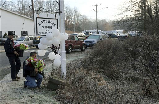 A couple of volunteer firefighters place flowers at a makeshift memorial at a sign for the Sandy Hook Elementary school, Saturday, Dec. 15, 2012 in Sandy Hook village of Newtown, Conn.  The massacre of 26 children and adults at Sandy Hook Elementary school elicited horror and soul-searching around the world even as it raised more basic questions about why the gunman, 20-year-old Adam Lanza, would have been driven to such a crime and how he chose his victims.   <span class=meta>(AP Photo&#47; Mary Altaffer)</span>