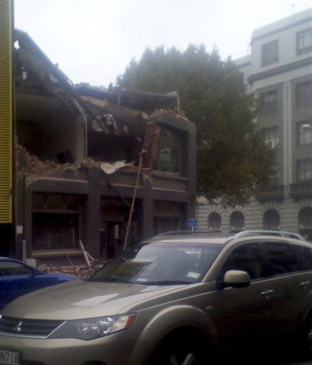 A car drives past a destroyed building in Christchurch central business district, New Zealand after a 6.3 earthquake hit Tuesday, Feb. 22, 2011.   <span class=meta>(AP Photo&#47; Samual  Sutherland)</span>