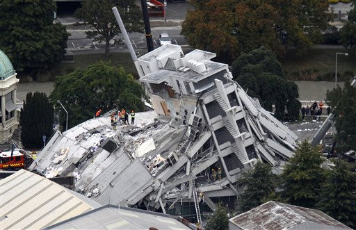Rescue workers climb onto the collapsed Pyne Gould Guinness Building in central Christchurch, New Zealand, Tuesday, Feb. 22 2011. A powerful earthquake collapsed buildings at the height of a busy workday killing at least 65 people and trapping dozens in one of the country&#39;s worst natural disasters.   <span class=meta>(AP Photo&#47; Mark Mitchell)</span>
