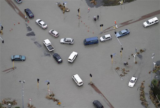 Cars are abandoned on a flooded street after a strong earthquake in suburban Christchurch, New Zealand, Tuesday, Feb. 22, 2011. The powerful earthquake collapsed buildings at the height of a busy workday killing at least 65 people and trapping dozens in one of the country&#39;s worst natural disasters.  <span class=meta>(AP Photo&#47; Mark Mitchell)</span>