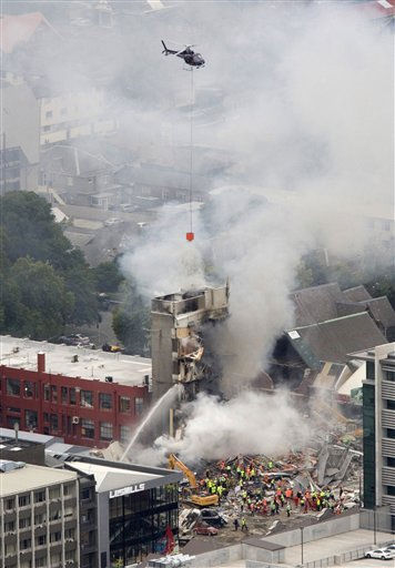ADDS NAME OF THE COLLAPSED BUILDING - Rescue workers and a helicopter work to extinguish a fire at a collapsed building of King&#39;s Education in central Christchurch, New Zealand, Tuesday, Feb. 22, 2011. A powerful earthquake collapsed buildings at the height of a busy workday killing at least 65 people and trapping dozens in one of the country&#39;s worst natural disasters. Several among a group of 23 Japanese exchange students and teachers at King&#39;s Education were still unaccounted for.   <span class=meta>(AP Photo&#47; Mark Mitchell)</span>