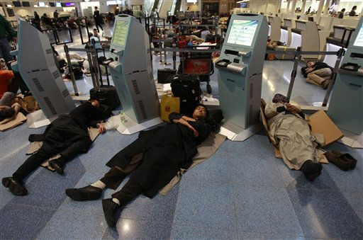 Travelers rest on the floor stranded at the Haneda international airport in Tokyo after a massive earthquake Friday, March 11, 2011. The ferocious tsunami spawned by one of the largest earthquakes ever recorded slammed Japan&#39;s eastern coasts. &#40;AP Photo&#47;Wally Santana&#41; <span class=meta>(AP Photo&#47; Wally Santana)</span>