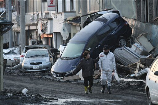 People walk by a car got stuck into a building in Miyako, Iwate Prefecture &#40;state&#41;, northern Japan, Saturday morning, March 12, 2011, a day after a strong earthquake-triggered devastating tsunami hit the area. &#40;AP Photo&#47;Takashi Ozaki, The Yomiuri Shimbun&#41;  JAPAN OUT, CREDIT MANDATORY <span class=meta>(AP Photo&#47; Takashi Ozaki)</span>