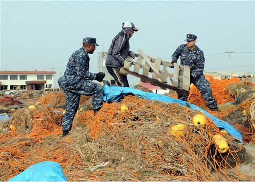 In a March 14, 2011 photo provided by the Navy Visual News Service, Navy Aerographer?s Mate 2nd Class John Dicola from New York, and Intelligence Specialist 1st Class Shakir Briggs from Orlando, Fla., helpa local civilian remove debris from the Misawa Fishing Port during a volunteer cleanup  in Misawa, Japan. More than 90 sailors from Naval Air Facility Misawa volunteered to help Misawa City employees and members of the community begin to clean up after an earthquake and tsunami. &#40;AP Photo&#47;Navy Visual News Service, Mass Communication Specialist 2nd Class Devon Dow&#41; <span class=meta>(AP Photo&#47; MC2 Devon Dow)</span>