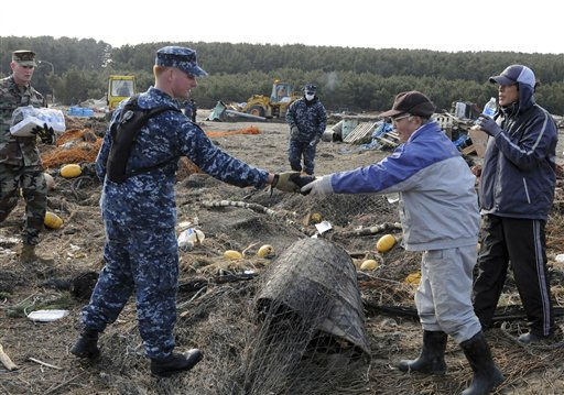 In a March 14, 2011 photo provided by the Navy Visual News Service, Mineman 2nd Class Cody Stone of Phoenix, Az., assigned to Naval Air Facility Misawa &#40;NAFM&#41;, recovers a spool of fisherman netting and returns it to a local civilian during a volunteer cleanup Monday, at the Misawa Fishing Port in Misawa, Japan.  &#40;AP Photo&#47;Navy Visual News Service, Mass Communication Specialist 2nd Class Devon Dow&#41; <span class=meta>(AP Photo&#47; MC2 Devon Dow)</span>
