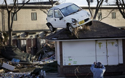 "<div class=""meta image-caption""><div class=""origin-logo origin-image ""><span></span></div><span class=""caption-text"">A man snaps a picture of the aftermath of tsunami following Friday's massive tsunami triggered by a powerful earthquake in Sendai, Miyagi prefecture, northern Japan, Saturday, March 12, 2011. (AP Photo/Junji Kurokawa) (AP Photo/ Junji Kurokawa)</span></div>"