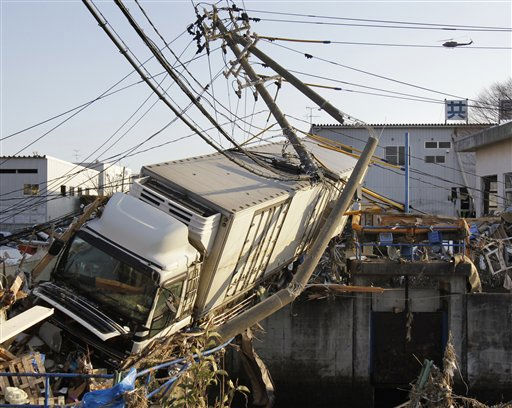 A huge trailer stuck in an narrow canal leans over debris at a port in Sendai, northern Japan, one day after a massive Tsunami triggered by a huge earthquake hit northern Japan Saturday, March 12, 2011.&#40;AP Photo&#47;Koji Sasahara&#41; <span class=meta>(AP Photo&#47; Koji Sasahara)</span>