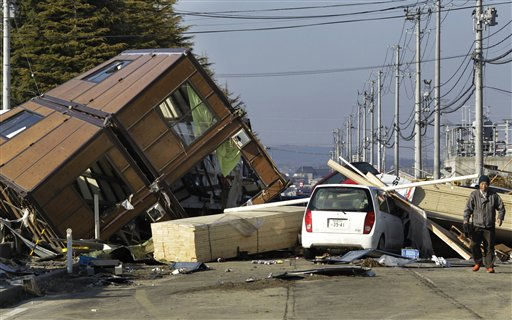A man walks by a collapsed house and debris at Sendai Port in Sendai, northeastern Japan, Saturday, March 12, 2011, following Friday&#39;s 8.9-magnitude quake and the tsunami it spawned hit the country&#39;s northeastern coast. &#40;AP Photo&#47;Koji Sasahara&#41; <span class=meta>(AP Photo&#47; Koji Sasahara)</span>