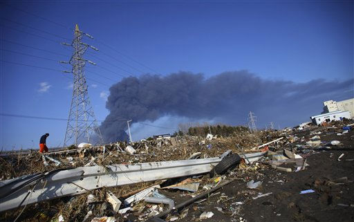 Smoke billows from a burning oil refinery as a man inspects damages done by a massive tsunami triggered by a powerful earthquake in Sendai, Miyagi prefecture, northern Japan, Saturday, March 12, 2011. &#40;AP Photo&#47;Junji Kurokawa&#41; <span class=meta>(AP Photo&#47; Junji Kurokawa)</span>