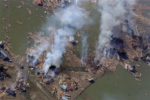 Smoke rises over an area in flood in Sendai, northern Japan, Saturday, March 12, 2011. Japan launched a massive military rescue operation Saturday after a giant, quake-fed tsunami killed hundreds of people and turned the northeastern coast into a swampy wasteland, while authorities braced for a possible meltdown at a nuclear reactor. &#40;AP Photo&#47;Itsuo Inouye&#41; <span class=meta>(AP Photo&#47; Itsuo Inouye)</span>
