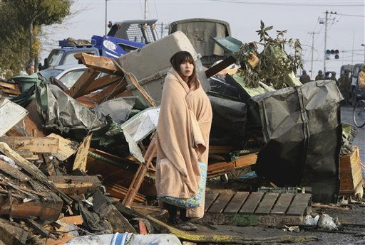 A woman wrapped up in a blanket stands in the middle of rubble, looking at the city submerged under water in Ishinomaki in Miyagi Prefecture &#40;state&#41; Sunday morning, March 13, 201, two days after the catastrophic earthquake-triggered tsunami hit the northeastern Japan. &#40;AP Photo&#47;The Yomiuri Shimbun, Tadashi Okkubo&#41;  JAPAN OUT, CREDIT MANDATORY <span class=meta>(AP Photo&#47; Tadashi Okubo)</span>