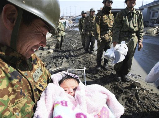CORRECTS CITY AND SOURCE - A Japan Self-Defense Force member reacts after rescuing a four-month-old baby girl in Ishinomaki, northern Japan, Monday, March 14, 2011, three days after a powerful earthquake-triggered tsunami hit the country&#39;s east coast. &#40;AP Photo&#47;The Yomiuri Shimbun, Hiroto Sekiguchi&#41; JAPAN OUT, CREDIT MANDATORY <span class=meta>(AP Photo&#47; Hiroto Sekiguchi)</span>