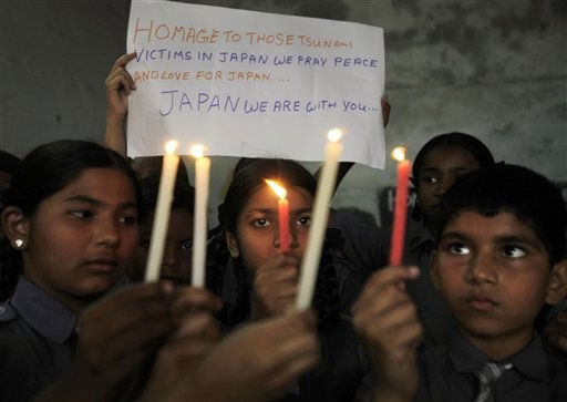 Indian school children pay homage to those killed in earthquake and tsunami in Japan as they hold lighted candles in Hyderabad, India, Monday, March 14, 2011. &#40;AP Photo&#47;Mahesh Kumar A.&#41; <span class=meta>(AP Photo&#47; Mahesh Kumar A)</span>