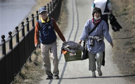 Evacuees carry belongings as a tsunami warning is issued following a massive tsunami triggered by March 11 earthquake in Tagajo near Sendai, Miyagi Prefecture, Japan, Monday, March 14, 2011. &#40;AP Photo&#47;Junji Kurokawa&#41; <span class=meta>(AP Photo&#47; Junji Kurokawa)</span>