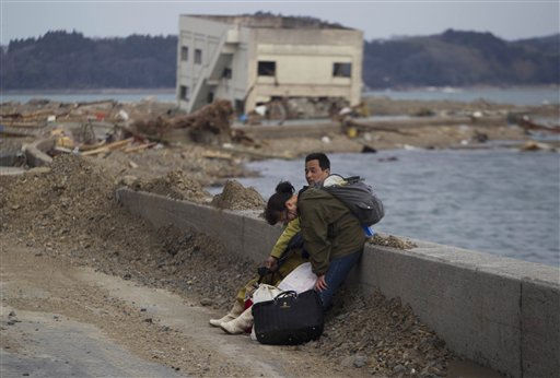 A Japanese couple stop to rest along a highway as they carry their belongings away form their destroyed village of Saito in northeastern Japan, Monday, March 14, 2011. Rescue workers used chain saws and hand picks Monday to dig out bodies in Japan&#39;s devastated coastal towns, as Asia&#39;s richest nation faced a mounting humanitarian, nuclear and economic crisis in the aftermath of a massive earthquake and tsunami that likely killed thousands. &#40;AP Photo&#47;David Guttenfelder&#41; <span class=meta>(AP Photo&#47; David Guttenfelder)</span>