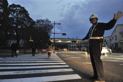 A police officer directs pedestrians and vehicles at an intersection during a rolling blackout in Fuji, Japan, Monday, March 14, 2011, three days after a powerful earthquake-triggered tsunami hit the country&#39;s east coast. &#40;AP Photo&#47;The Yomiuri Shimbun, Noriaki Sasaki&#41; JAPAN OUT, MANDATORY CREDIT <span class=meta>(AP Photo&#47; Noriaki Sasaki)</span>