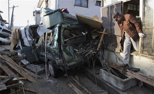 A man climbs out the window of his heavily damaged home Monday, March 14, 2011, in Yotsukura, Japan, three days after a giant quake and tsunami struck the country&#39;s northeastern coast. &#40;AP Photo&#47;Gregory Bull&#41; <span class=meta>(AP Photo&#47; Gregory Bull)</span>