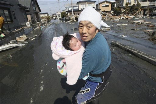 Upon hearing another tsunami warning, a father tries to flee for safety with his just reunited four-month-old baby girl who was spotted by Japan&#39;s Self-Defense Force member in the rubble of tsunami-torn Ishinomaki Monday, March 14, 2011, three days after a powerful earthquake-triggered tsunami hit northeast Japan. &#40;AP Photo&#47;The Yomiuri Shimbun, Hiroto Sekiguchi&#41; JAPAN OUT, CREDIT MANDATORY <span class=meta>(AP Photo&#47; Hiroto Sekiguchi)</span>