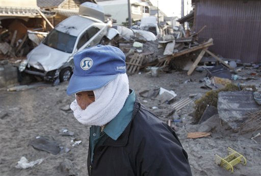 A man, with his face covered to protect against dust, looks out at the damage Monday, March 14, 2011, in Yotsukura, Japan, three days after a giant quake and tsunami struck the country&#39;s northeastern coast. &#40;AP Photo&#47;Gregory Bull&#41; <span class=meta>(AP Photo&#47; Gregory Bull)</span>