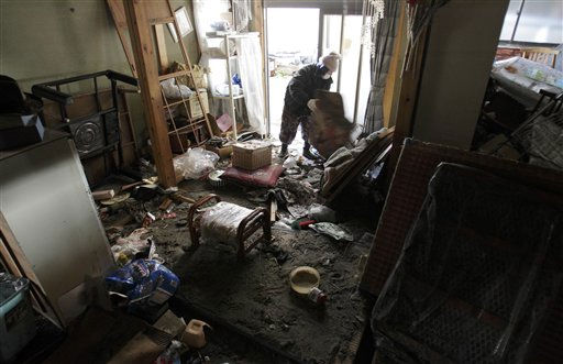 A man searches for salvageable items in his home Monday, March 14, 2011, in Yotsukura, northern Japan, three days after a giant quake and tsunami struck the country&#39;s northeastern coast. &#40;AP Photo&#47;Gregory Bull&#41; <span class=meta>(AP Photo&#47; Gregory Bull)</span>