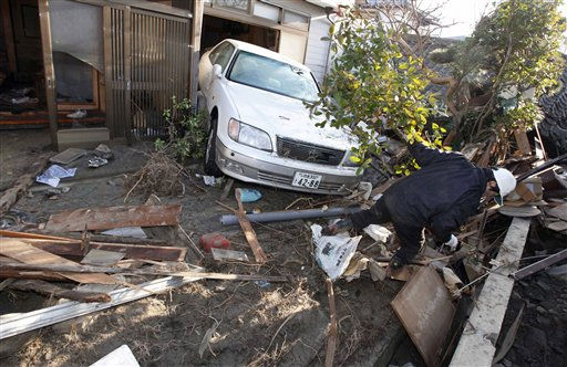 A resident of the seaside town of Yotsukura, northern Japan, clears debris from his homes Monday, March 14, 2011, three days after a giant quake and tsunami struck the country&#39;s northeastern coast. &#40;AP Photo&#47;Mark Baker&#41; <span class=meta>(AP Photo&#47; Mark Baker)</span>