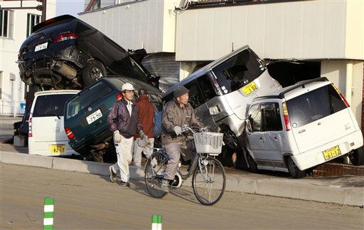 A resident cycles past wrecked cars in the seaside town of Yotsukura, northern Japan, Monday, March 14, 2011, three days after a giant quake and tsunami struck the country&#39;s northeastern coast. &#40;AP Photo&#47;Mark Baker&#41; <span class=meta>(AP Photo&#47; Mark Baker)</span>