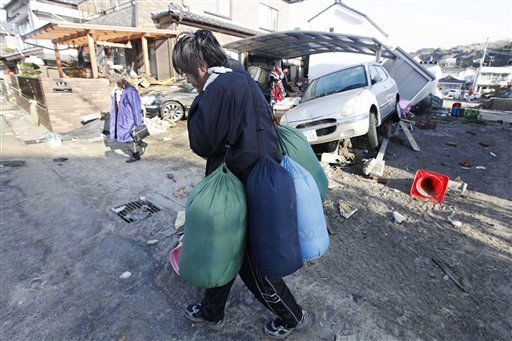 "<div class=""meta ""><span class=""caption-text "">A resident of the seaside town of Yotsukura, Japan, carries sleeping bags as they clear debris from their home Monday, March 14, 2011, three days after a giant quake and tsunami struck the country's northeastern coast. (AP Photo/Mark Baker) (AP Photo/ Mark Baker)</span></div>"