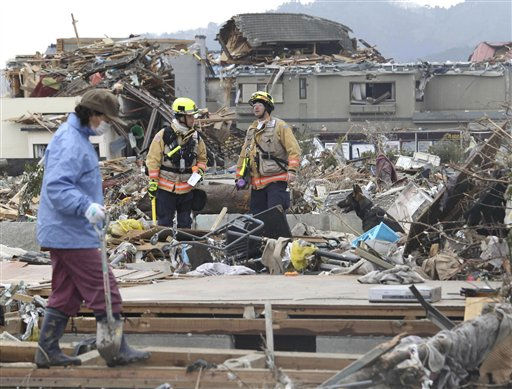 "<div class=""meta ""><span class=""caption-text "">A tsunami survivor, left, looking for belongings from where her house was standing walks by U.S. rescue team members with a sniff dog working in debris in Ofunato in Iwate Prefecture (state), northeastern Japan, Tuesday, March 15, 2011, four days after a massive earthquake and tsunami slammed northeastern Japan. (AP Photo/Yomiuri Shimbun, Masamichi Genkoh) JAPAN OUT, MANDATORY CREDIT (AP Photo/ Masamichi Genkoh)</span></div>"
