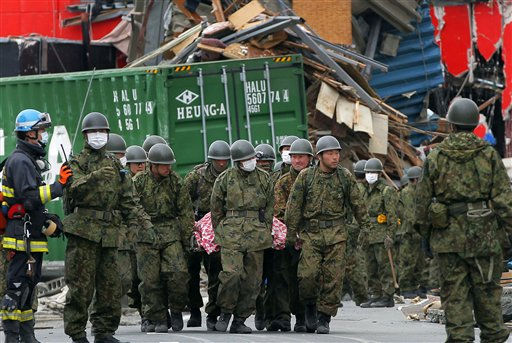 "<div class=""meta ""><span class=""caption-text "">Members of the Japan Ground Self-Defense Force carry the body of a victim at the tsunami-hit area in Ofunato, Iwate Prefecture Tuesday, March 15, 2011, four days after an earthquake and tsunami devastated Japan's northeast coast towns. (AP Photo/Itsuo Inouye) (Photo/Itsuo Inouye)</span></div>"