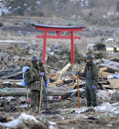 Soldiers of Japan Ground Self-Defense Force search though the rubble at an earthquake and tsunami-hit area in Kesennuma, Miyagi Prefecture, northeastern Japan, Thursday, March 17, 2011. &#40;AP Photo&#47;Kyodo News&#41; <span class=meta>(Photo&#47;Anonymous)</span>