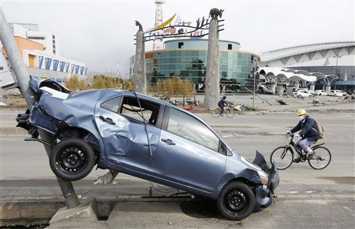 "<div class=""meta ""><span class=""caption-text "">A man cycles past a wrecked car following the March 11 earthquake triggered tsunami at the port in Sendai, Japan, Thursday, March 17, 2011. (AP Photo/Mark Baker) (Photo/Mark Baker)</span></div>"