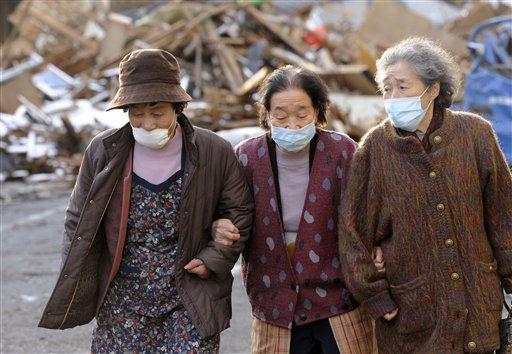 Masked women walk together after visiting the site where their houses stood before Friday&#39;s earthquake and tsunami, in Kamaishi, Iwate Prefecture, northern Japan, Thursday, March 17, 2011.  <span class=meta>(Photo&#47;Anonymous)</span>