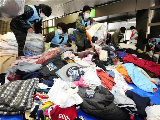 Volunteers sort out clothing that were just delivered to them prior to distribution to quake victims at Fukushima, northeastern Japan, on Thursday, March 17, 2011 following last week&#39;s massive earthquake and resulting tsunami. &#40;AP Photo&#47;Kyodo News&#41; <span class=meta>(Photo&#47;Anonymous)</span>