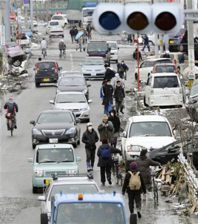 People walk along with cars on an earthquake and tsunami-hit area in Ishinomaki, Miyagi Prefecture , northeastern Japan, Thursday, March 17, 2011. &#40;AP Photo&#47;Kyodo News&#41; <span class=meta>(Photo&#47;Anonymous)</span>