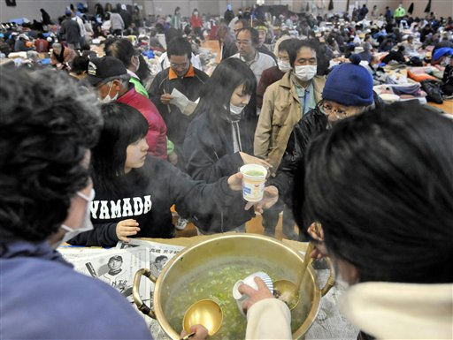 Evacuees receive bowls of fish soup from local fishermen at a makeshift shelter in Yamada, northern Japan, Thursday, March 17, 2011, after Friday&#39;s powerful earthquake-triggered tsunami hit Japan&#39;s northeast coast. &#40;AP Photo&#47;Kyodo News&#41; <span class=meta>(Photo&#47;Anonymous)</span>