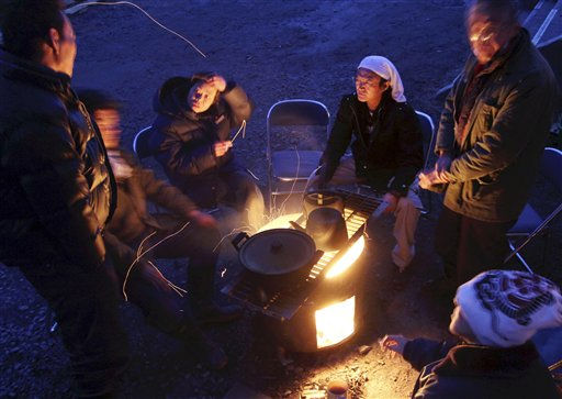 "<div class=""meta ""><span class=""caption-text "">Survivors huddle around the open fire to keep warm at a shelter in Minamisanriku town, Miyagi Prefecture, northeastern Japan, Friday, March 18, 2011, just one week after a massive earthquake and resulting tsunami. (AP Photo/Yomiuri Shimbun, Ichiro Ohara) (Photo/Ichiro Ohara)</span></div>"