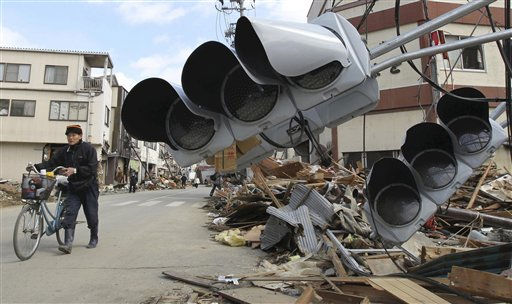 "<div class=""meta ""><span class=""caption-text "">A man pushes a bicycle along street where the debris was removed in the devastated city of Kesennuma, northeastern Japan, on Friday, March 18, 2011, just one week after a massive earthquake and resulting tsunami. (AP Photo/Yomiuri Shimbun, Kaname Muto) (Photo/Kaname Muto)</span></div>"