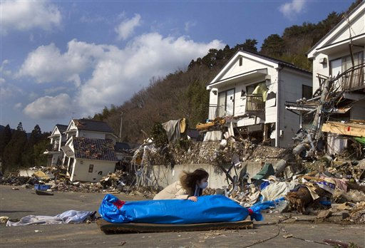 Tayo Kitamura, 40, kneels in the street to caress and talk to the wrapped body of her mother Kuniko Kitamura, 69, after Japanese firemen discovered the dead woman inside the ruins of her home in Onagawa, northeastern Japan Saturday, March 19, 2011. &#40;AP Photo&#47;David Guttenfelder&#41; <span class=meta>(AP Photo&#47; David Guttenfelder)</span>