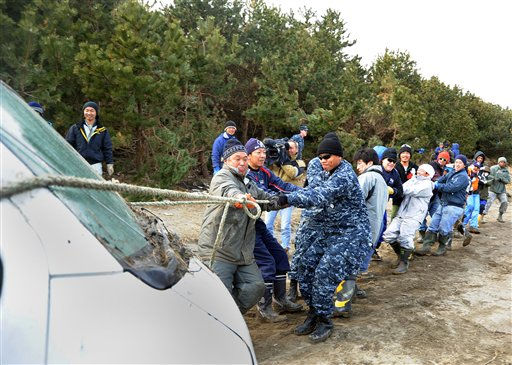 In this photo released by the U.S. Navy, service members and Misawa residents pull a damaged vehicle from the woods near the Misawa port in Japan on Saturday, March 19, 2011. Service members, civilian employees, and family members from Naval Air Facility Misawa are helping residents clean up the port following an earthquake that caused a devastating tsunami along Japan&#39;s eastern coast. &#40;AP Photo&#47;U.S. Navy, Mass Communication Specialist 1st Class Matthew M. Bradley&#41; <span class=meta>(AP Photo&#47; MC1 Matthew Bradley)</span>