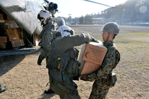 In this Friday, March 18, 2011 picture provided by the U.S. Navy, Chief Naval Air Crewman Francisco Garcia, center, delivers Meals Ready-to-Eat to a Japan Ground Self-Defense Force soldier in Yamada, Japan. The aircrew, assigned to Helicopter Mine Countermeasures Squadron &#40;HM&#41; 14, delivered 360 cases of water and eight pallets of MREs. &#40;AP Photo&#47;U.S. Navy, Lt. Eric Quarlesr&#41; <span class=meta>(AP Photo&#47; Lt. Eric Quarlesr)</span>