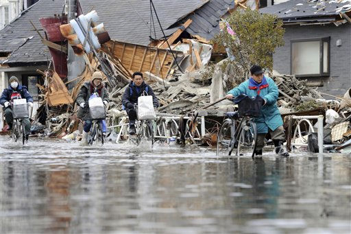 eople wade through a road flooded with seawaters by spring tide in Ishinomaki, Miyagi Prefecture, Japan, Monday, March 21, 2011. &#40;AP Photo&#47;The Yomiuri Shimbun, Kunihiko Miura&#41;  <span class=meta>(Photo&#47;Kunihiko Miura)</span>