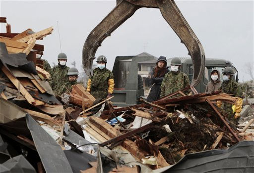 Family members watch Japan Ground Self Defense Force personnel search for remains of a fellow family member in their home in Natori, Miyagi Prefecture, Japan, Monday, March 21, 2011, following the March 11 earthquake and tsunami that devastated the northeast coast of Japan. &#40;AP Photo&#47;Mark Baker&#41; <span class=meta>(Photo&#47;Mark Baker)</span>