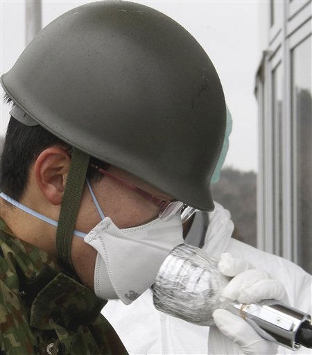 Japan Self-Defense Force&#39;s member receives a radiation exposure scanning after they carry elderly persons who live in a house about 20 miles &#40;30 kilometers&#41; from the Fukushima Dai-ichi nuclear plant in the March 11 earthquake and tsunami-destroyed city of  Minamisoma, northern Japan Tuesday, March 22, 2011.  <span class=meta>(AP Photo&#47; Koichi Nakamura)</span>
