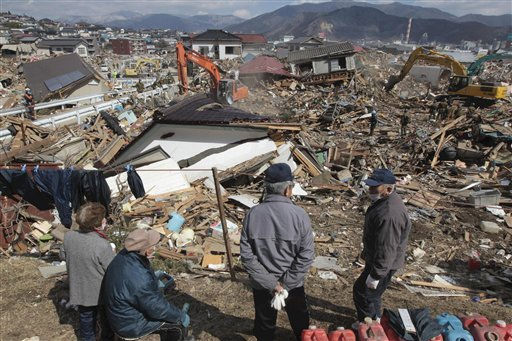 Survicors watch their smashed home being removed by earth movers at the devastated city of Ofunato, northeastern Japan, Thursday, March 24, 2011, following the March 11 earthquake and resulting tsunami that struck Japan&#39;s northeastern coast. &#40;AP Photo&#47;The Yomiuri Shimbun, Hiroto Nomoto&#41; JAPAN OUT, MANDATORY CREDIT <span class=meta>(AP Photo&#47; Hiroto Nomoto)</span>