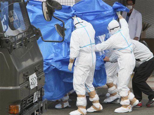 "<div class=""meta image-caption""><div class=""origin-logo origin-image ""><span></span></div><span class=""caption-text"">Japan's Self-Defense Force's members and others in protective gear help to transfer workers who stepped into contaminated water on Thursday during their operation at the Fukushima Dai-ichi nuclear plant, at a hospital in Fukushima, northern Japan Friday, March 25, 2011. (AP Photo/Yomiuri Shimbun, Takuya Yoshino) JAPAN OUT, MANDATORY CREDIT (AP Photo/ Takuya Yoshino)</span></div>"